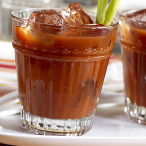 Classic V8 Bloody Mary cocktail in small glass with celery