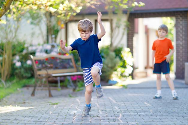 kidplaying hopscotch outside