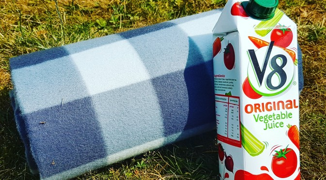 V8 carton with picnic blanket on grass